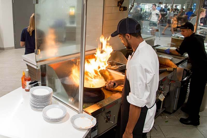 A chef in a white chef's jacket holds a flaming pan over the stove top.
